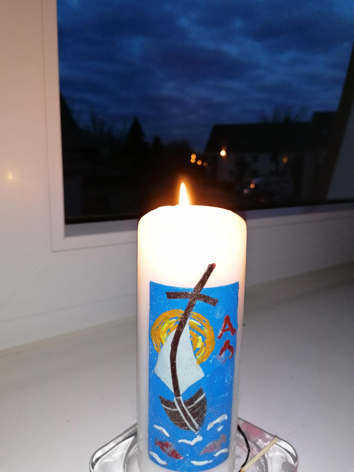 So vertreiben in den Fenstern unseres Wohnzimmers jeden Abend die Osterkerzen der letzten Jahre die Dunkelheit, grüßt JE aus Holtenau